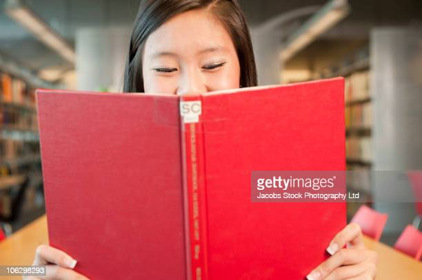 Smiling Chinese student reading book in library