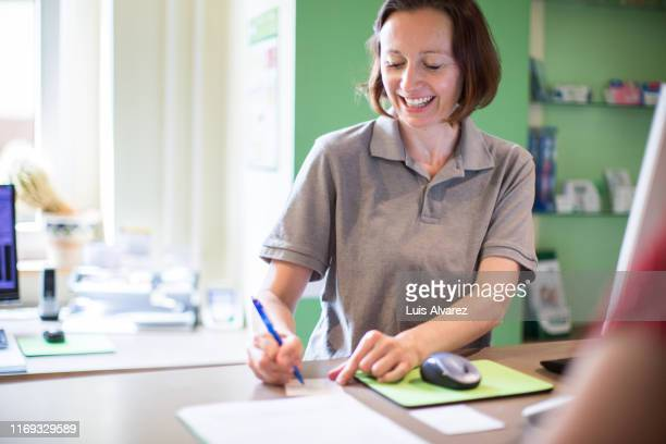 smiling clinic receptionist making a health card for a patient - arzthelferin stock-fotos und bilder