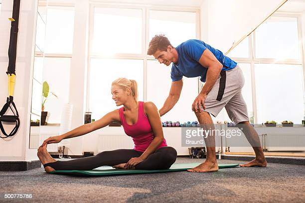 Smiling coach assisting young woman in doing stretching exercises.