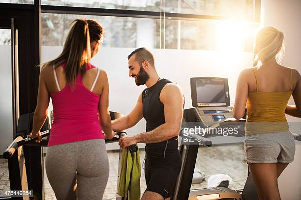Smiling coach helping a woman to adjust speed on treadmill.