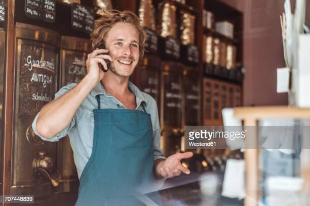 smiling coffee roaster in his shop on the phone - attività foto e immagini stock