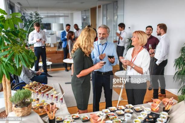 lächelnde kollegen genießen essen und gespräch auf der party - launch event stock-fotos und bilder