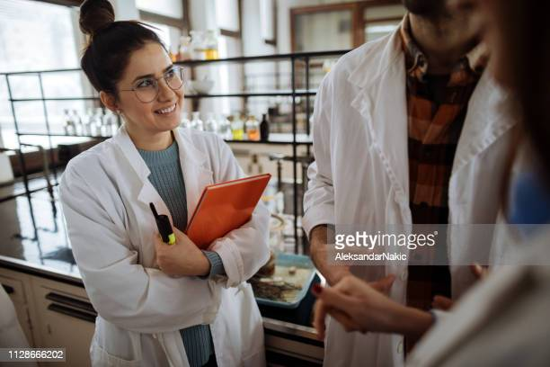 smiling colleagues in chemical laboratory - microbiologist stock pictures, royalty-free photos & images