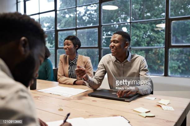 smiling colleagues in conference room at workplace - africa stock pictures, royalty-free photos & images