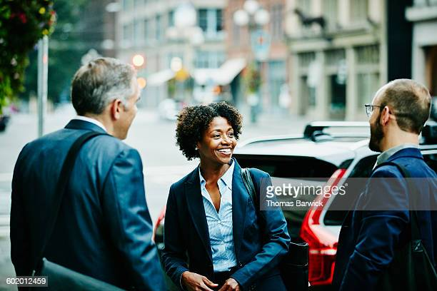 smiling colleagues in discussion on sidewalk - leanincollection stock pictures, royalty-free photos & images