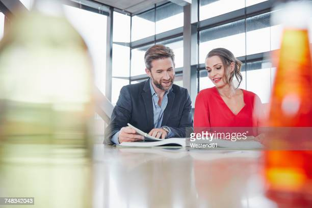 Smiling colleagues in office looking at large book