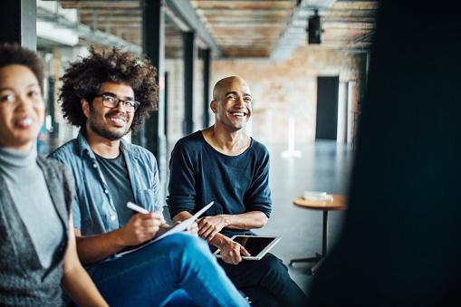 Smiling colleagues listening in meeting - gettyimageskorea