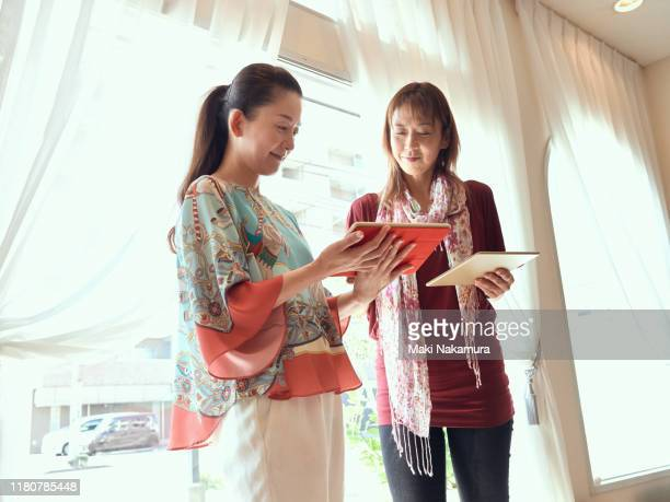 smiling colleagues looking at data on digital tablet in studio office - maebashi city stock photos and pictures