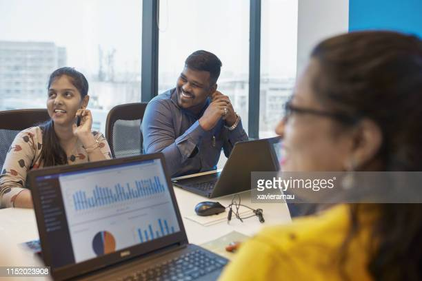 smiling colleagues planning strategy in board room - employee engagement stock pictures, royalty-free photos & images