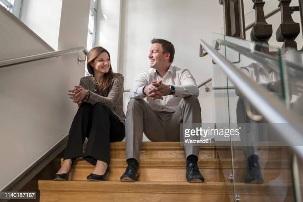 Smiling colleagues sitting in staircase talking