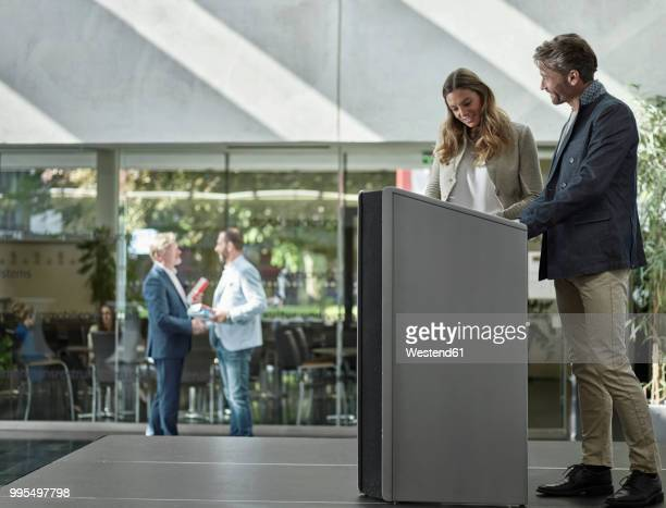 Smiling colleagues standing on stage at lectern