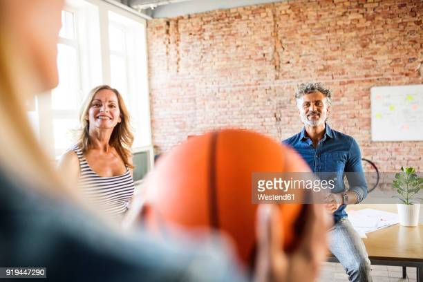 Smiling colleagues with basketball in office