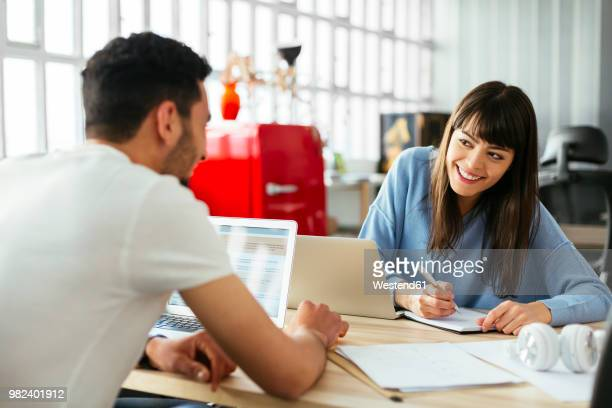 smiling colleagues working at desk in office - flirtare foto e immagini stock