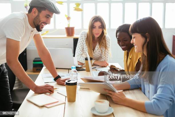 smiling colleagues working together at desk in office - quatre personnes photos et images de collection