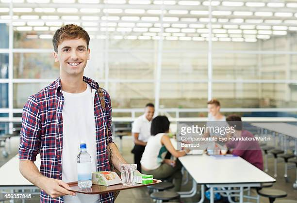 Smiling college student in cafeteria with food