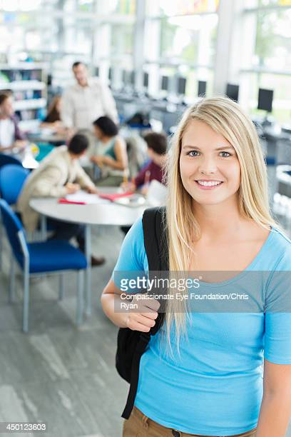 Smiling college student standing in classroom