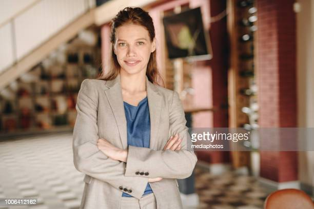 Smiling confident attractive young business lady in formal jacket crossing arms on chests and looking at camera in restaurant