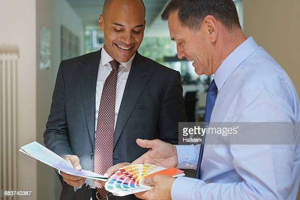 Smiling confident businessmen discussing over color swatches at creative office