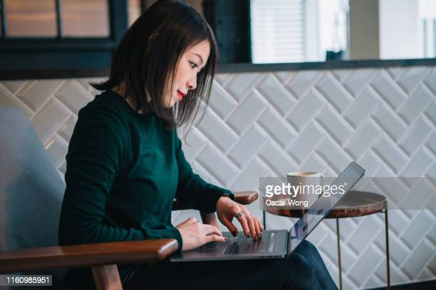 smiling, confident, modern businesswoman checking email at laptop in office - hotel stock pictures, royalty-free photos & images