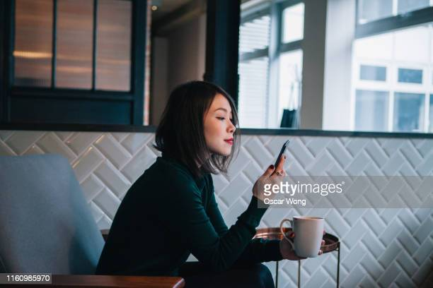 smiling, confident, modern businesswoman taking coffee break and checking social media at mobile phone in office - hotel stock pictures, royalty-free photos & images
