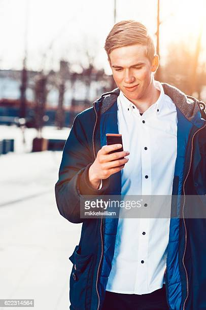 Smiling consumer uses smart phone and looks at the screen