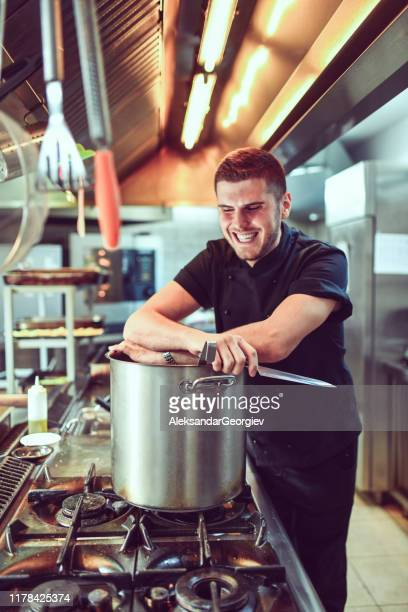 smiling cook ready to chop vegetables for his stew boiling in the pot - course meal stock pictures, royalty-free photos & images