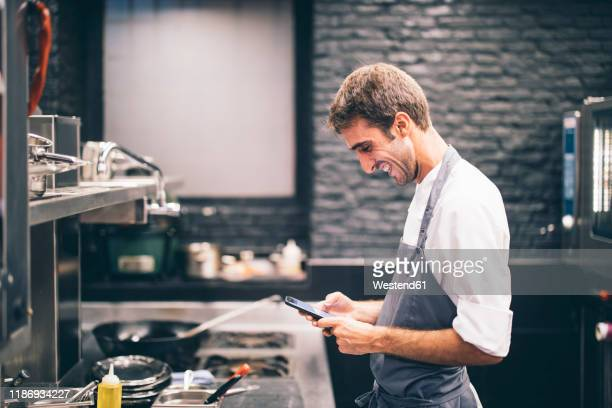 smiling cook using smartphone in the kitchen of a restaurant - gifted movie stock pictures, royalty-free photos & images