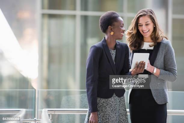 Smiling corporate businesswomen using digital tablet