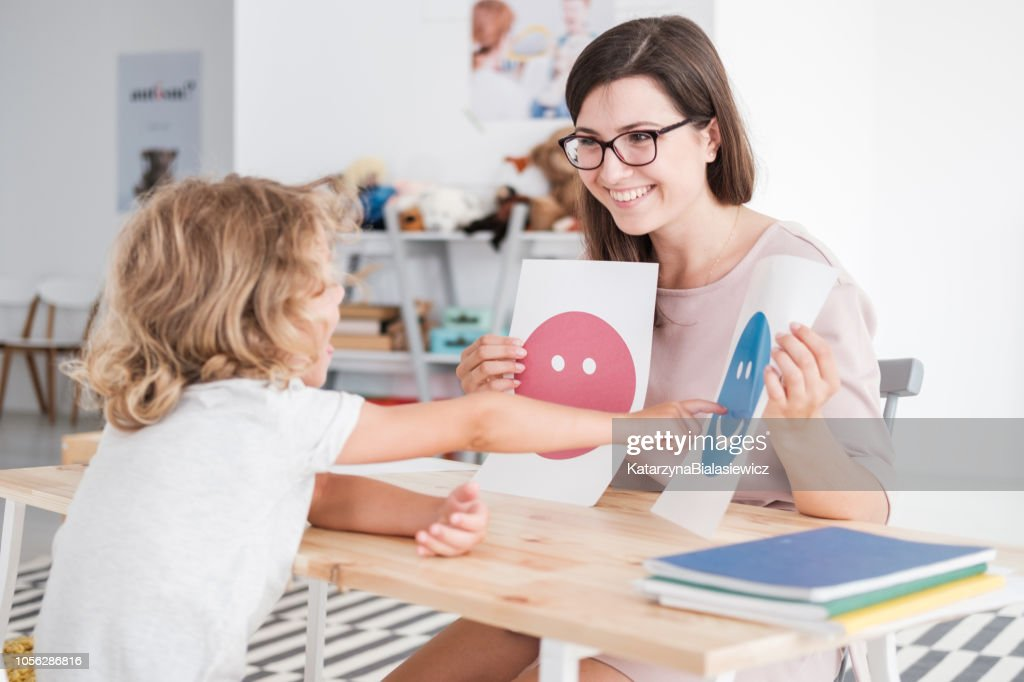 Smiling counselor holding pictures during meeting with young patient with autism : Stock Photo