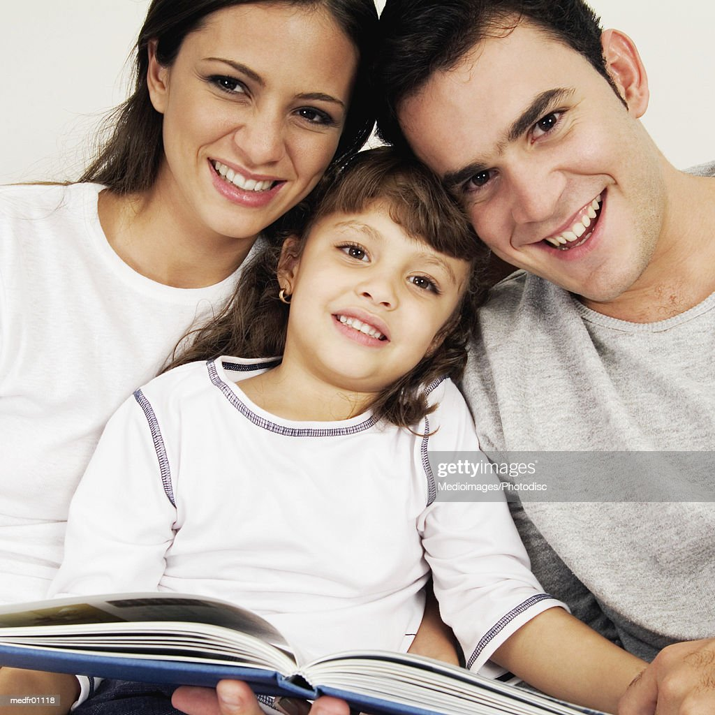 Smiling couple and child with scrapbook, close-up : Stock Photo