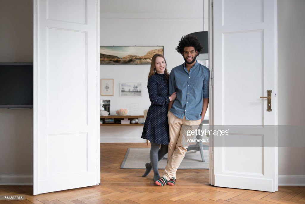 Smiling couple at home standing in door frame : Stock Photo