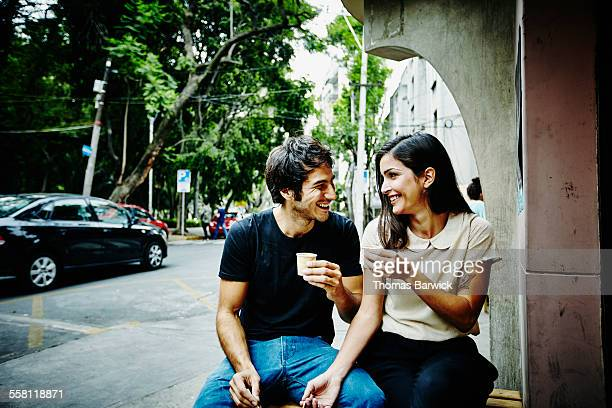 Smiling couple at sidewalk cafe drinking espresso