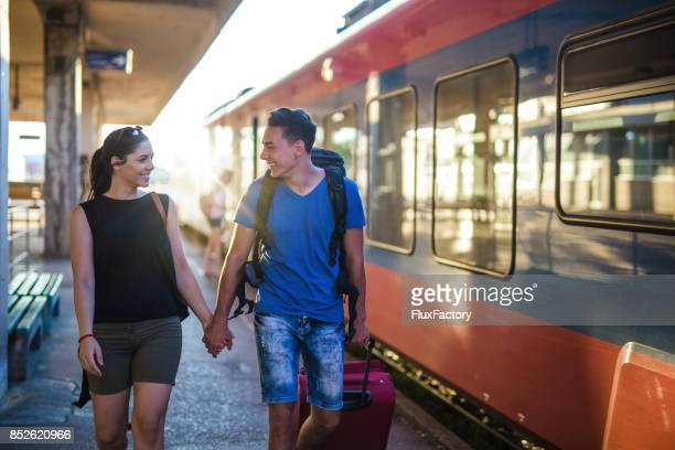 smiling couple at train station - long distance relationship stock pictures, royalty-free photos & images