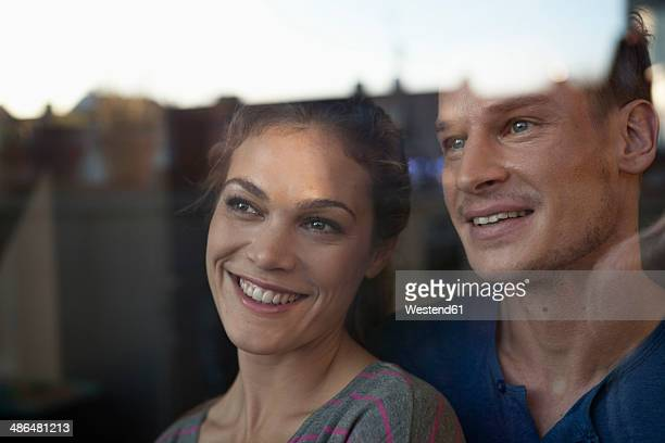 Smiling couple behind window