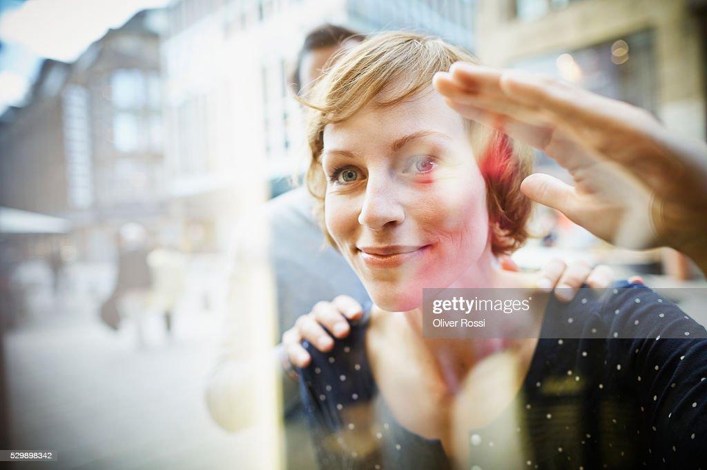 Smiling couple behind window : Stock Photo