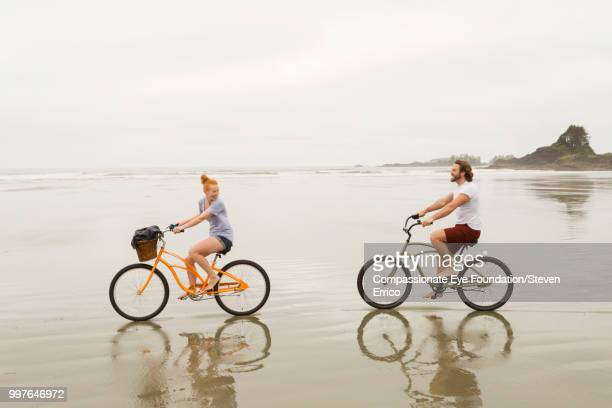 smiling couple bike riding on beach - maroon stock pictures, royalty-free photos & images