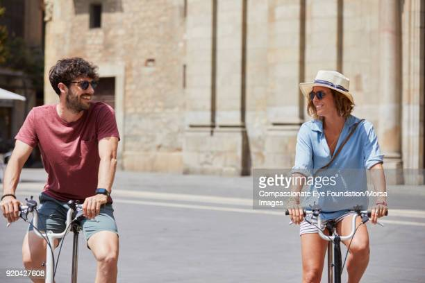Smiling couple bike riding on street in Barcelona