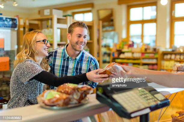smiling couple buying meat in small market - health food shop stock pictures, royalty-free photos & images