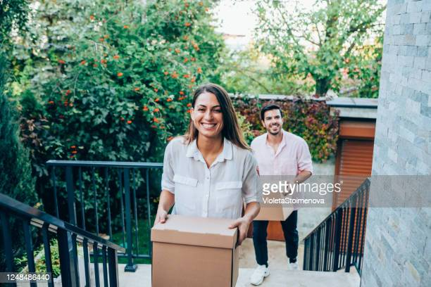 smiling couple carrying boxes into their new house. - home ownership stock pictures, royalty-free photos & images