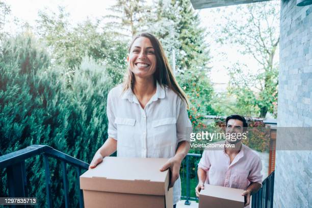smiling couple carrying boxes into their new house. - entering stock pictures, royalty-free photos & images
