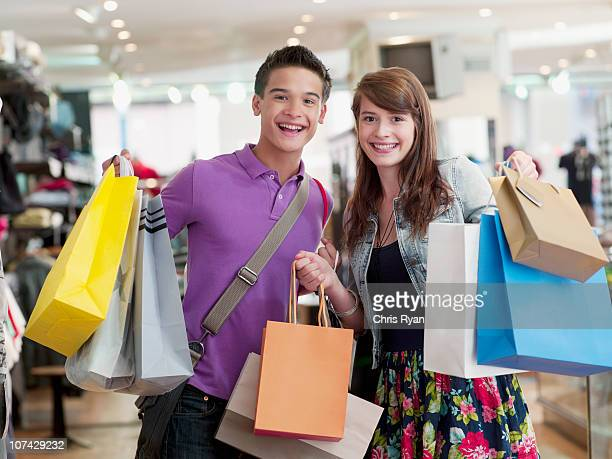 smiling couple carrying shopping bags in store - kingston upon thames stock photos and pictures
