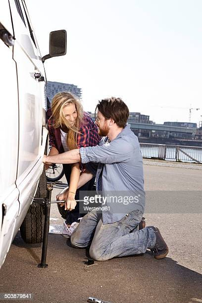 smiling couple changing car tyre at minivan - puncturing stock pictures, royalty-free photos & images