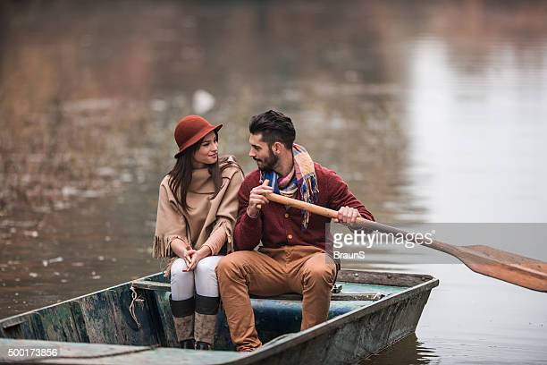 Smiling couple communicating in a boat during autumn day.