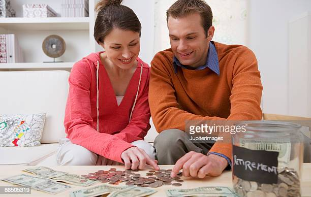 Smiling couple counting coins