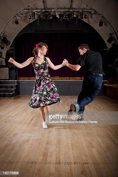 Smiling couple dancing in auditorium