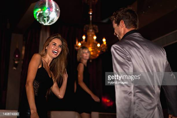 smiling couple dancing in club - elegantie stockfoto's en -beelden