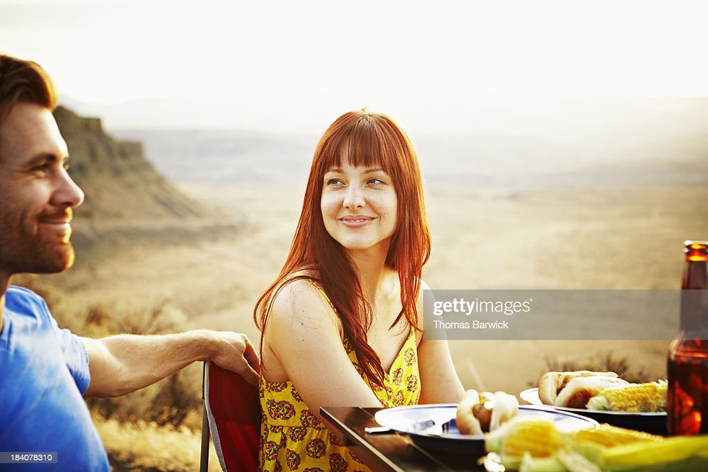 Smiling couple dining at table at sunset : Stock Photo