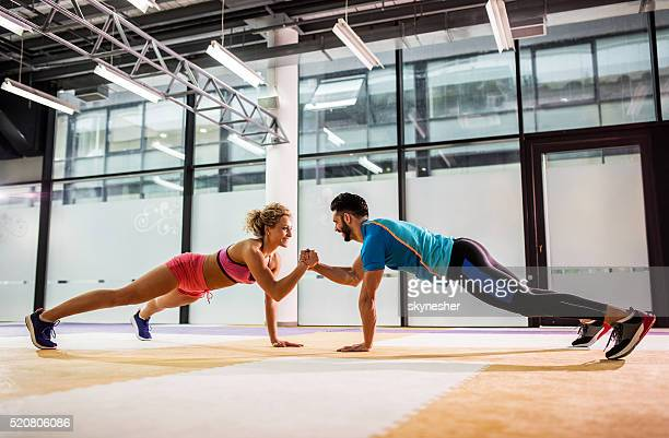 Smiling couple doing push-ups together in a gym.