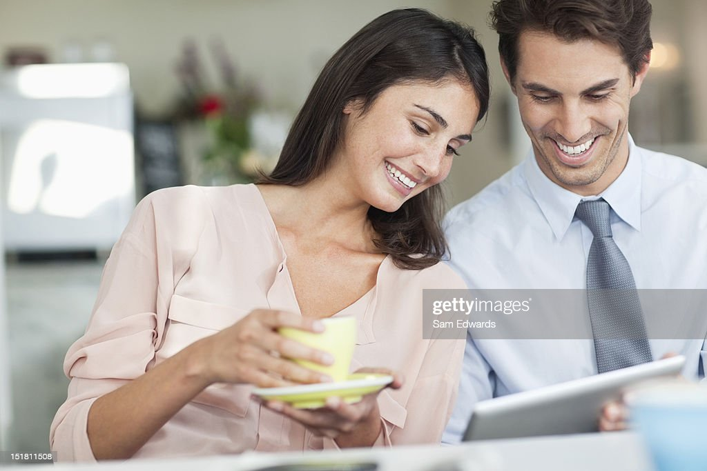 Smiling couple drinking coffee and using digital tablet in cafe window : Stock Photo