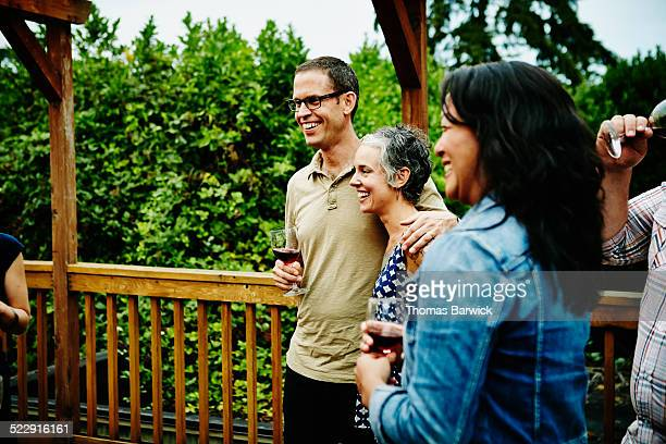Smiling couple drinking wine with friends on patio